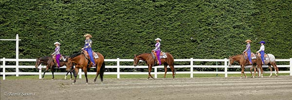 young women on horses in a corral